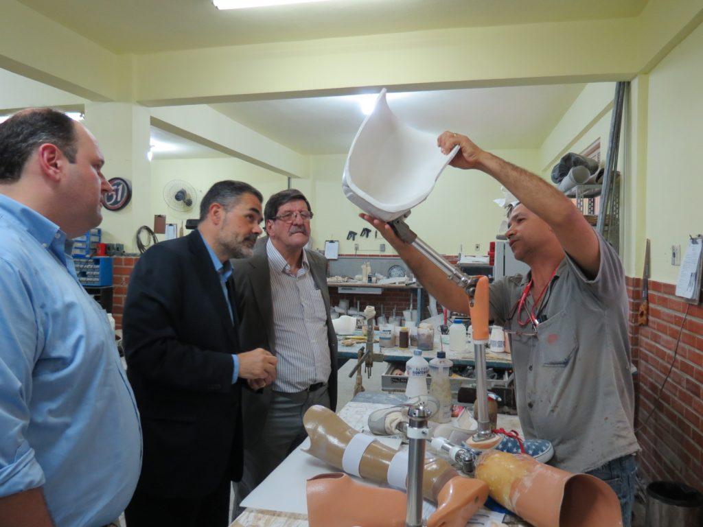 Alberto Matucci e Marcio Laureano, com o diretor Pietro Acceta, da Pestalozzi, observam o técnico da Pestalozzi explicar como funciona a prótese de perna.